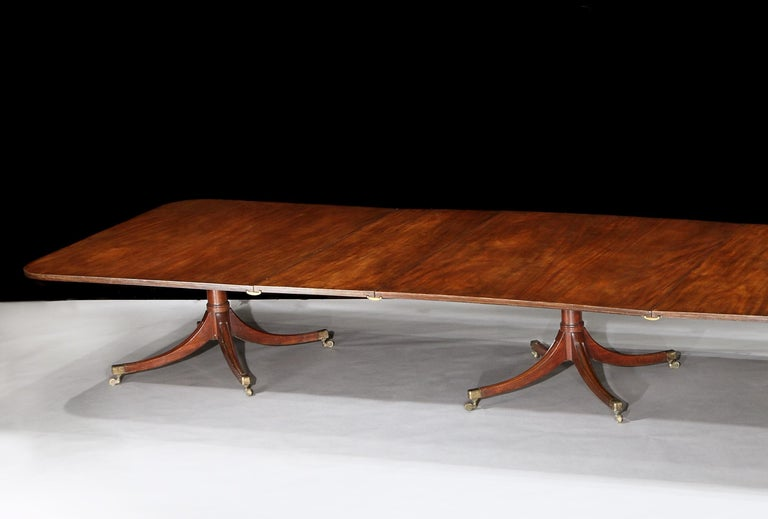 A fabulous George III mahogany four pedestal dining table, the superbly figured mahogany rectangular tops, with a reeded edge and three extra leaves, resting on four shot of turned gun barrel pedestals with brass box casters.