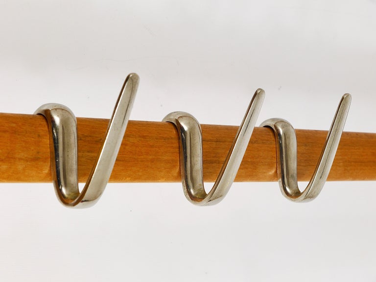 An elegant modernist coat rack from the 1950s, designed and executed by the Austrian designer Carl Auböck. Made of beech with eight rare nickel-plated