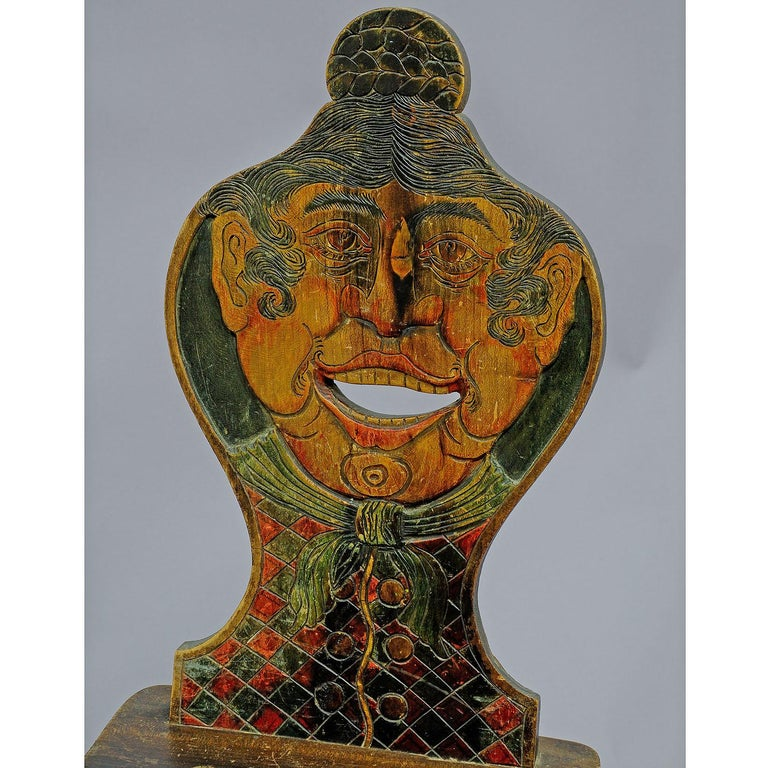 A carved and painted folksy chair. Backrest carved and painted as Tyrolian woman. Executed circa 1910, in Austria or Bavaria. Backrest partly with dark staining.  Measures: Width 16.93
