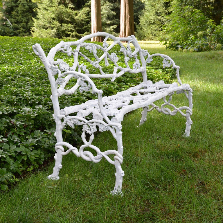 """A fine """"Oak Tree"""", or rustic twig, pattern cast-iron seat, the naturalistic arched back, seat and arms cast as branches with acorn clusters, on conforming trunk feet joined by entwined serpents."""