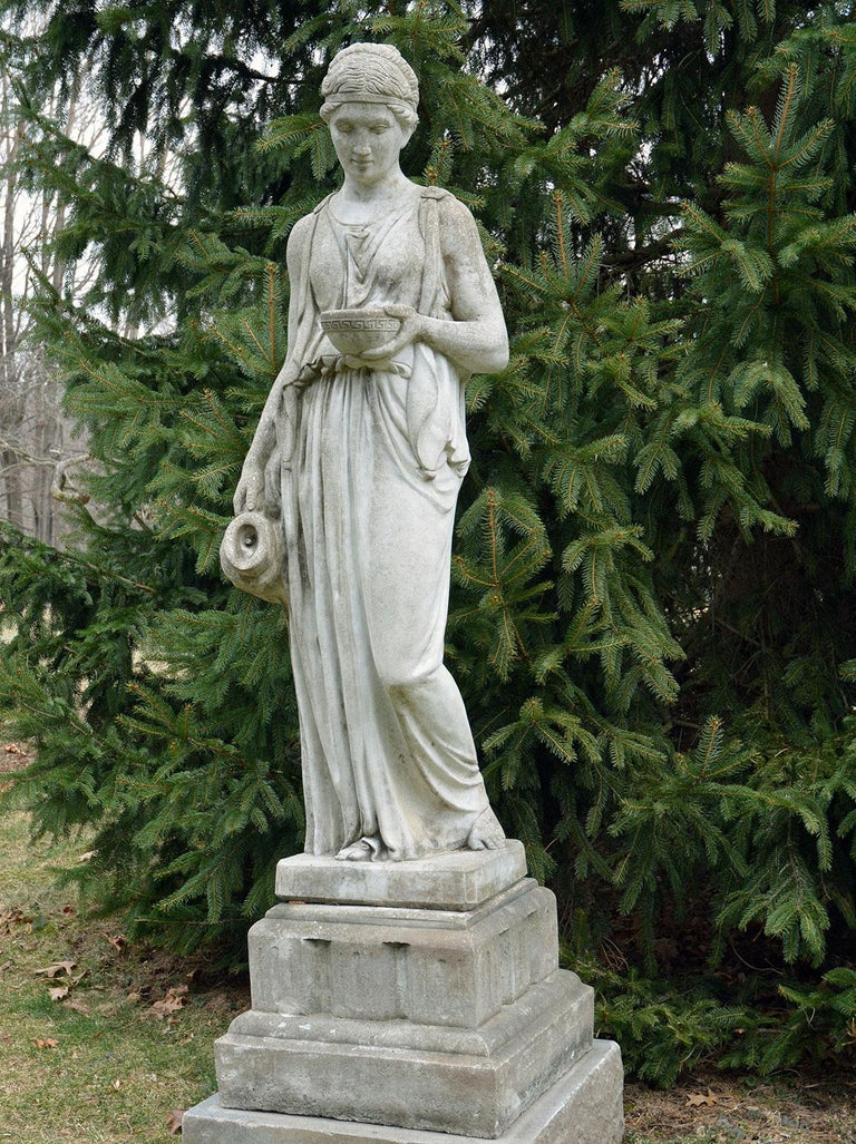 A composition stone figure of Hebe, the goddess of youth and the cupbearer to the gods and goddesses of Mount Olympus, shown in classical dress, holding a cup in her proper left hand and a ewer in her proper right, the figure standing on a stepped