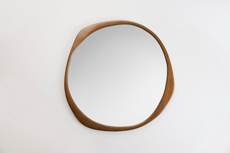 The sculptural A.Cepa Mirror in Hand-Patina Bronze is cast in bronze at a fine art foundry in Pennsylvania, and skillfully finished by hand. Undulating and irregular in form, the A. Cepa mirror is the focal point in any room with its captivating