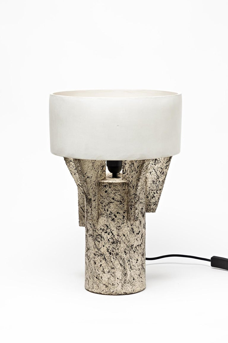A ceramic table lamp by Denis Castaing with white glaze decoration.
