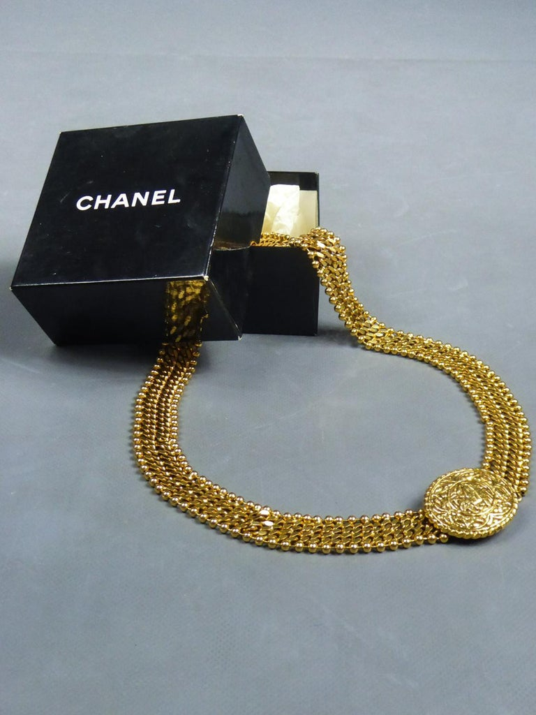 Circa 1970/1980 France  Beautiful evening belt in golden metal signed by Chanel and dating from the 1970s / 1980s. Assembly of two extensible links chains polished on their ends, edged with shiny golden metal ball chains. Oval belt buckle in golden