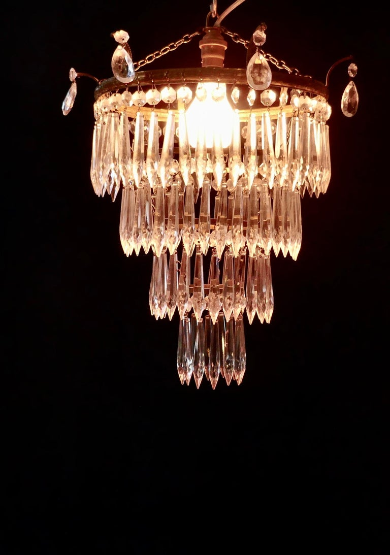 A charming Art Deco 4-tier waterfall pendant chandelier   A charming waterfall tiered pendant chandelier, this delicate light has four layers of crystal icicle pendants hanging from a circular brass age darkened frame   This fine quality