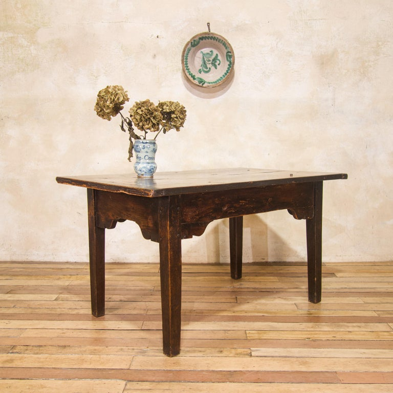 A charming mid 18th century joined oak farmhouse table. Demonstrating a two plank top with cleated ends, above an arched apron, on square tapering legs.