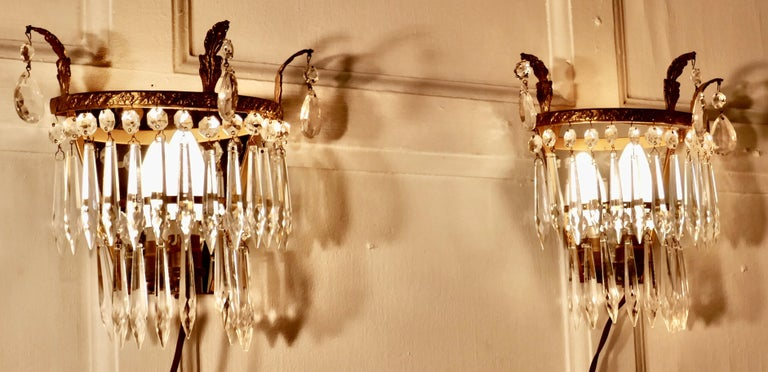 A charming pair of waterfall chandelier wall lights   A charming pair of chandelier wall lights, these delicate lights have 2 layers of cut glass pendants hanging from a brass frame, at the back of each light there is a mirror giving a splendid