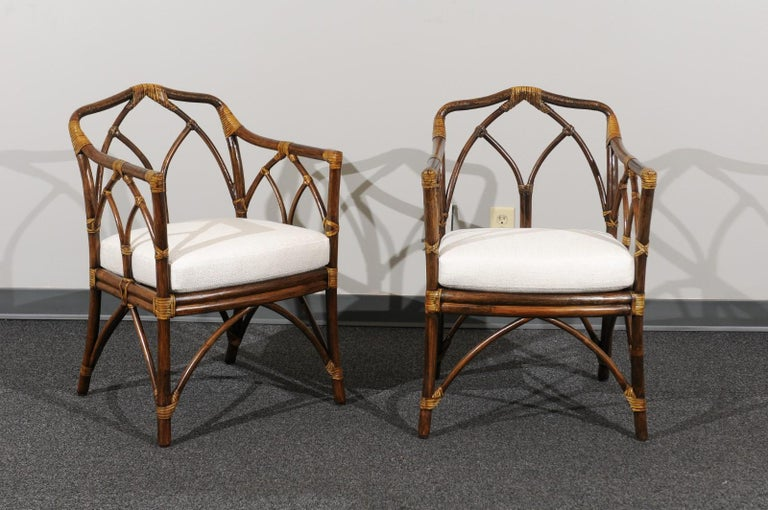 A radiant restored set of eight (8) difficult to find modern arm dining chairs by McGuire, circa 1975. Stunning expertly crafted rattan and cane construction with an exquisite Cathedral back detail. Handsome accent bindings in the Maker's iconic