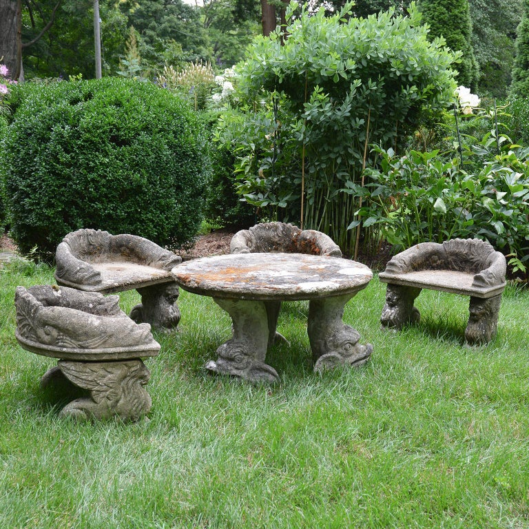 A composition stone children's furniture set comprised of four armchairs and a round table, the chairs with stylized fish-form arms and griffin supports, the table with dolphin supports. Measures: Table 16.5 ins. high, 31 ins. diameter, chairs 19.5