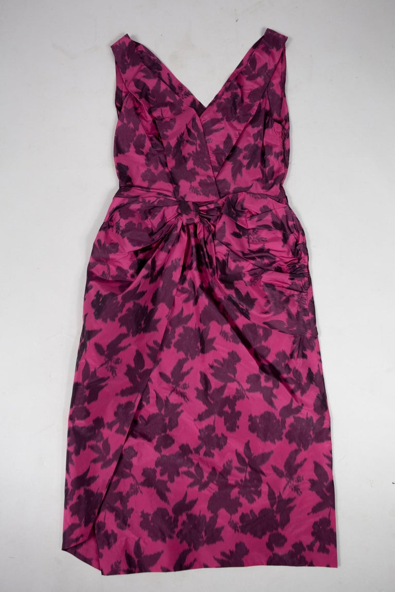 Circa 1955/1960  France  Beautiful cocktail dress in fuschia printed chiné taffeta of bouquets of wine-colored flowers and dating from the years 1955/1960. Sleeveless dress with large plunging V-neckline and pleated in two crossed sides. Sheath