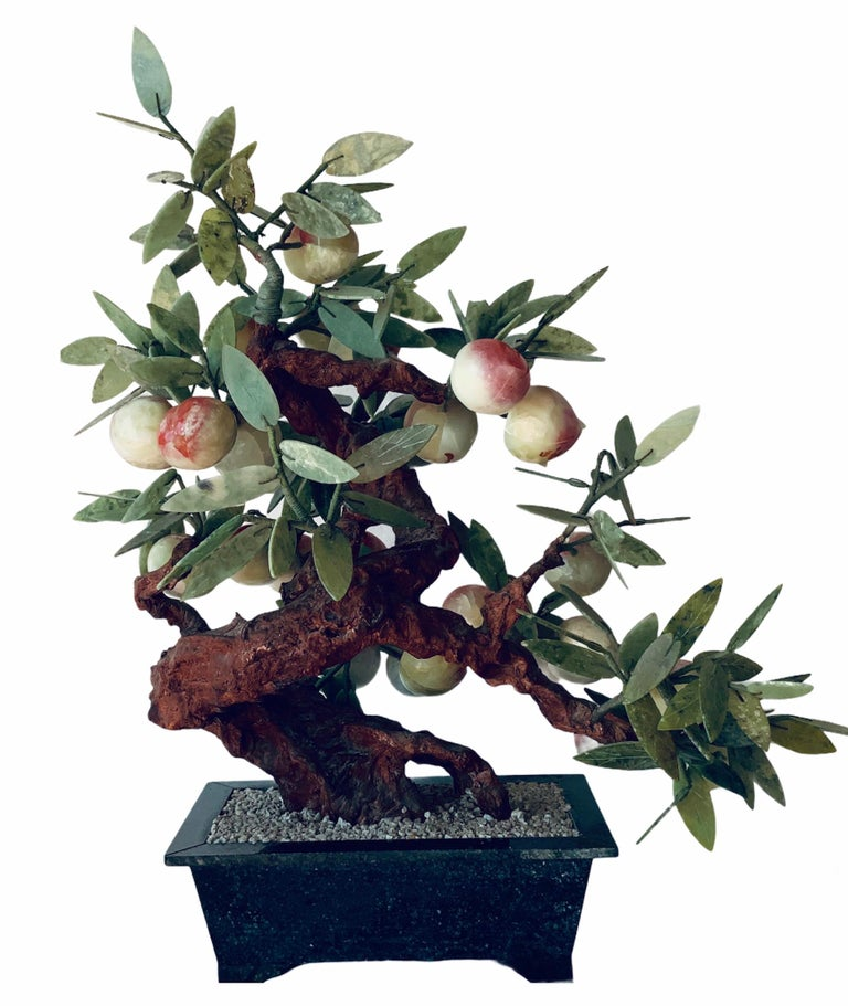 This is a peach tree bonsai. The peaches are made of coral yellow green colored hardstones and the leaves are made of nephrite jade. The tree is standing in a dark green marble rectangular planter that is full of white pebbles. There are some