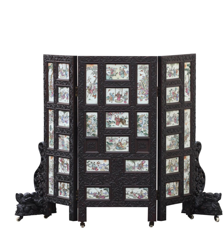 A Chinese three-panel porcelain inlaid and mixed wood screen The frame mounted with thirty famille-rose panels painted with various figures, animals and auspicious objects Measures: Height 41.25 in. x width 58 in. (104.7 x 147 cm.)