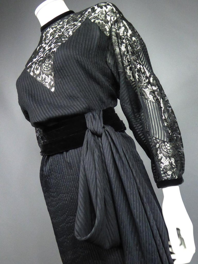 Spring Summer 1982 Collection France  Haute Couture or cocktail little black dress in muslin and Caudry lace from the designer house Christian Dior directed by Marc Bohan. Straight dress with batwing sleeves and interesting pointed cutouts in Caudry