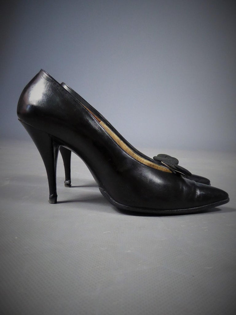 Circa 1960 France  Pair of Christian Dior evening heels by Roger Vivier in glossy black leather from the 60s. Shoes with stiletto heels, curved shape and pointed at the front, decorated with a removable rosette in black fluted silk ottoman. Inside
