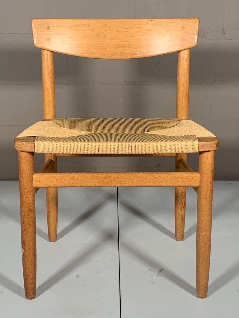 A classic oak and natural rush (papercord) dining or desk chair by Børge Mogensen. Newly redone seat, oak has a nice vintage patina. The chair is comfortable and is wider than most chairs of this style.