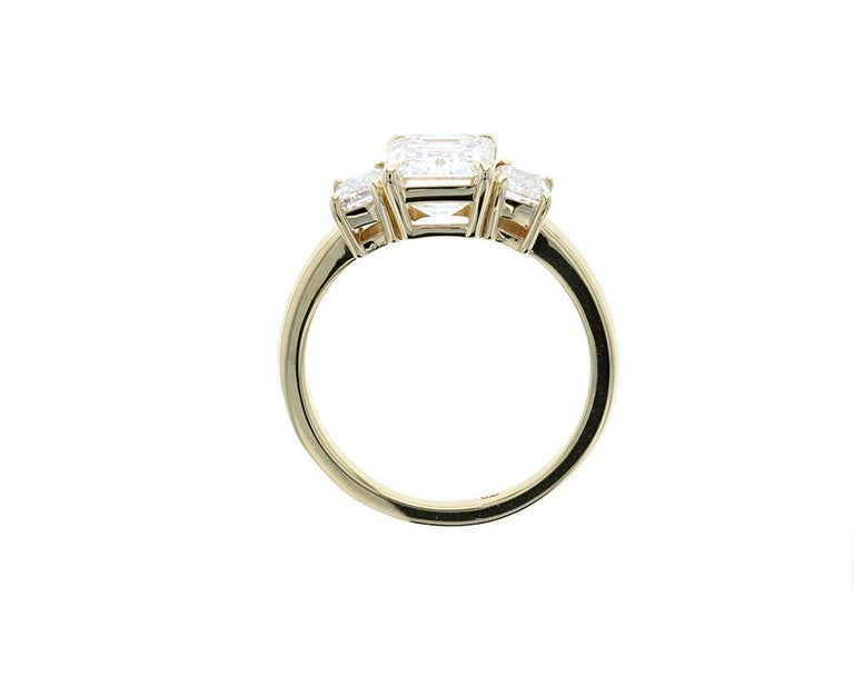 In a seamless blend of elements evocative of old-world glamour and modern elegance, this exquisite emerald cut diamond engagement ring features two matching emerald cut diamond sides stones. With a yellow gold shank and eagle claw prongs, the center