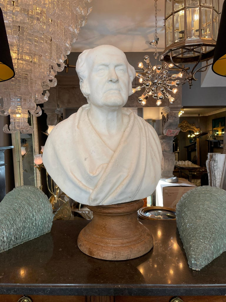 A well carved life size bust in statuary Carrara marble. The subject dressed in classical Roman attire, signed by the artist and sculpture Achille Casoni. Standing on an oak Socle, an old repair to his nose, however in original condition. A very