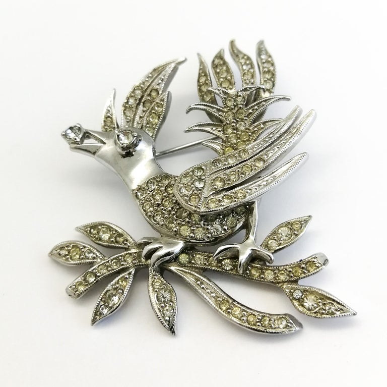 This beautiful 'gem' of a brooch, represents a bird, sitting on a branch, holding a single 'jewel' or 'diamond' in its beak. Beautifully crafted in rhodium metal and clear paste by Mitchel Maer for Christian Dior in the early 1950s, it is a part of