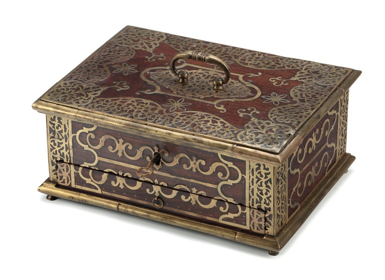 AN INDIAN ROSEWOOD AND EBONY BRASS MOUNTED BOX FOR THE ISLAMIC MARKET     Malabar Coast, 18th century    With a large drawer with several compartments under a lid with two compartment interior, with brass mounts and chased brass decoration,
