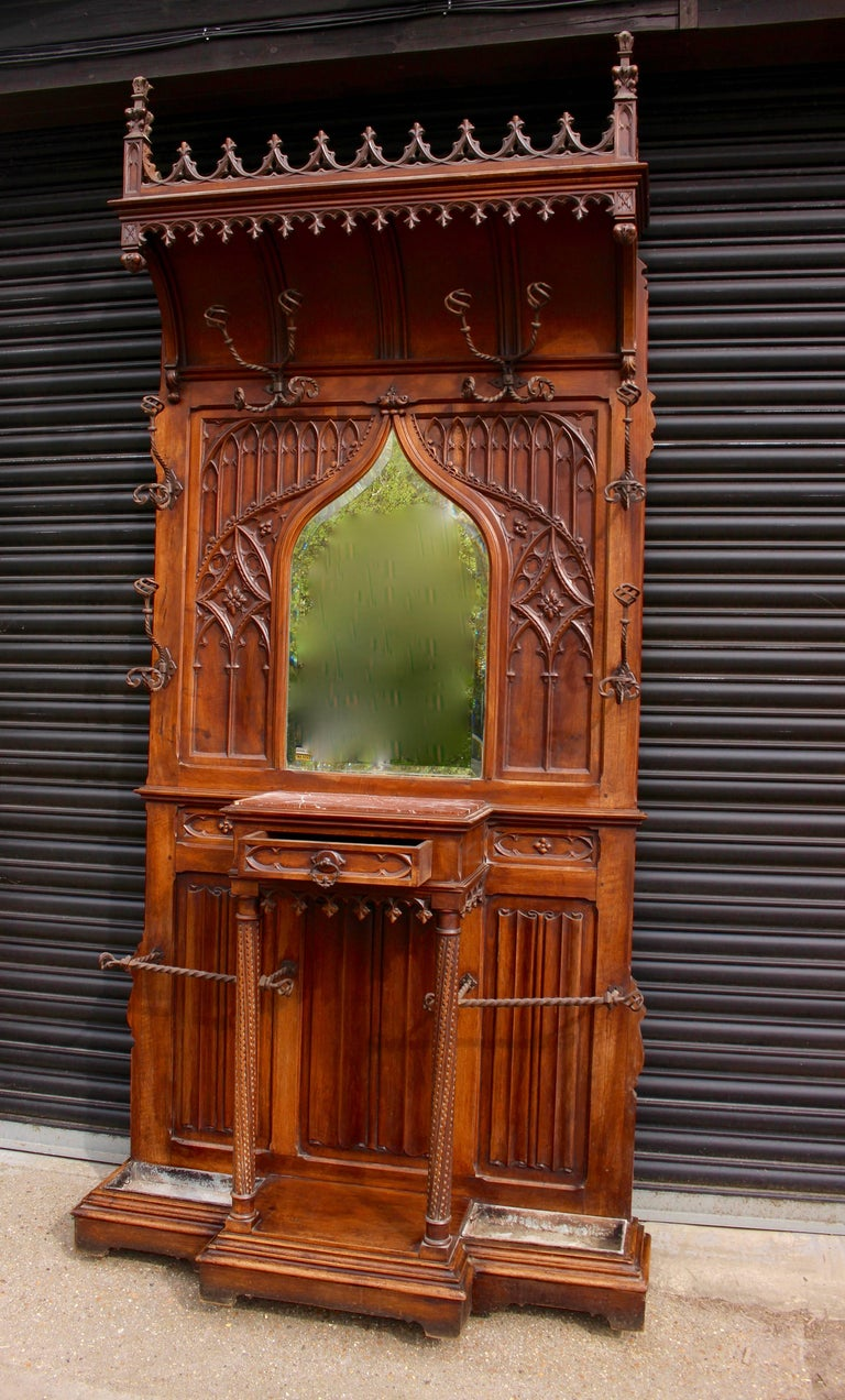 A simply stunning and imposing Gothic Revival hall stand. Having a profusely carved upper cornice with finials. Having a central bevelled mirror surrounded by gothic arches and carving. Below the mirror is a rouge marble-topped centre table with a