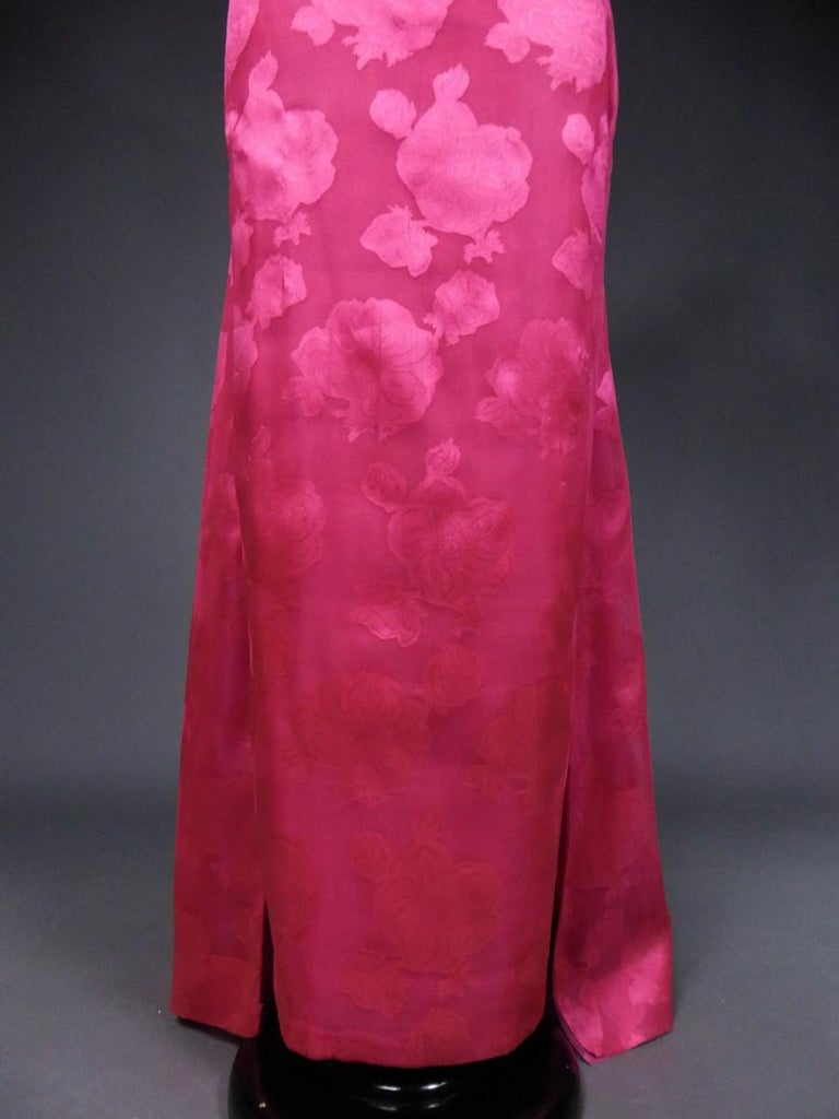 Circa 1957/1960 Paris France  A damask chiffon or brocade organza silk evening dress with large fuchsia blooming roses and rosebuds by Cristobal Balenciaga. Strapless finely pleated bodice, deep neckline and zipper in the back. Long sheer skirt