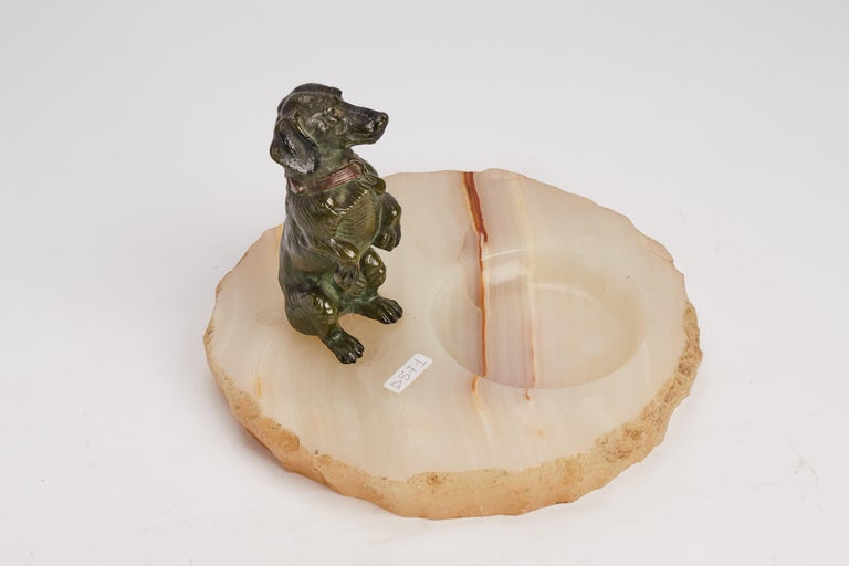 The base of the ashtray is made out of pale marble lightly veined. On one side the ashtray, on the other a sculpture of a dachshund. Vienna 1890.