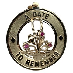 """A Date to Remember"" 1950s 14 Karat Yellow Gold Charm with Pink Sapphires"