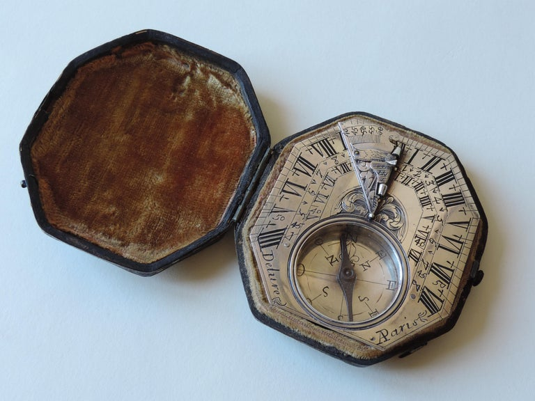 Signed Delure A Paris, the octagonal dial with hinged gnomon and bird pointer, four engraved hour scales, inset compass and engraved on reverse with towns and their latitudes, 2¾ins (7cm) long.