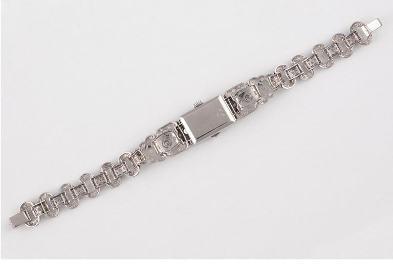 The rectangular dial with Arabic chapters, the bezel set with single-cut diamonds, the openwork lugs with scroll detailing and set with vari-cut diamonds, to a fancy-link bracelet of old brilliant-cut diamonds, mounted in platinum, millegrain detail