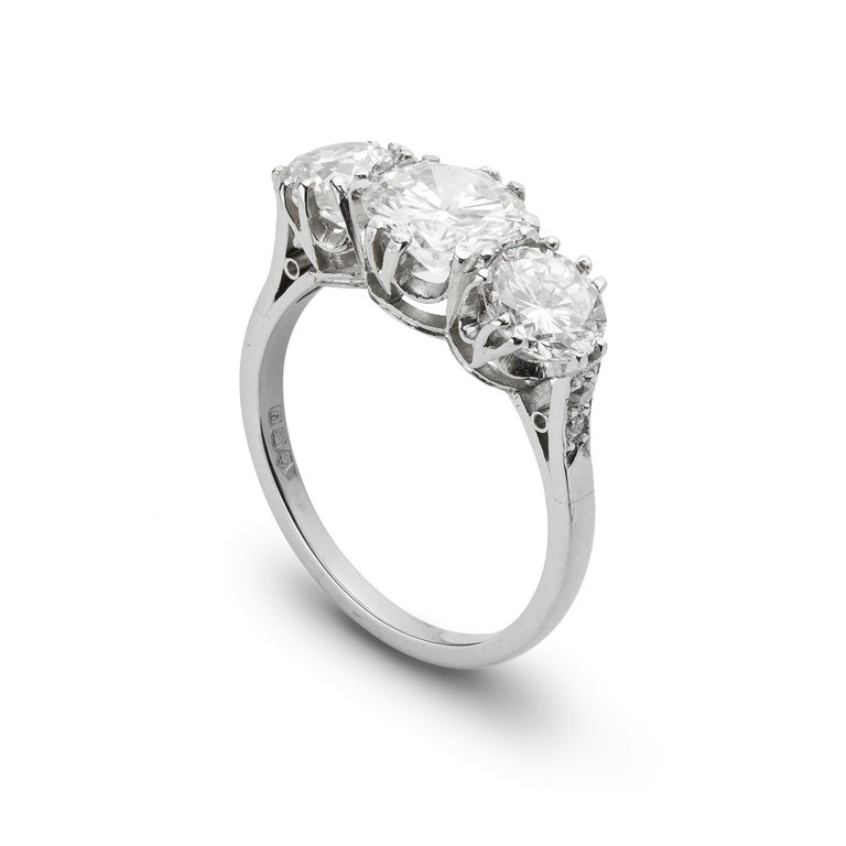 A diamond three stone ring, the central round brilliant-cut diamond weighing 1.05 carats and the outer diamonds a further total of 1.18 carats, split claw set to a platinum mount with diamond set chenier shoulders, hallmarked platinum London 1998,