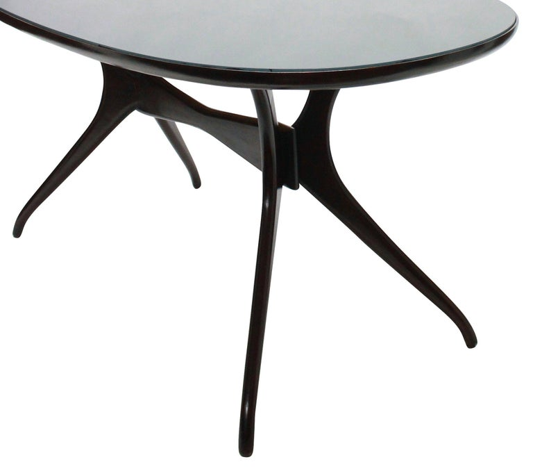An Italian dining table with a sculptural base in mahogany coloured wood with a blue/grey glass inset top.