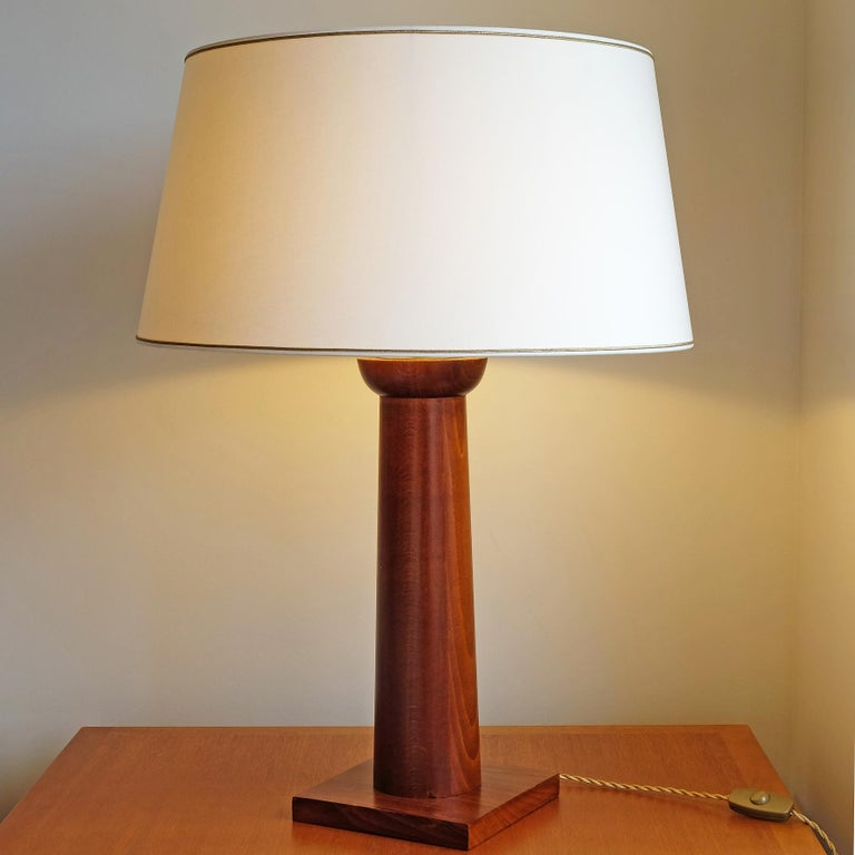 A beech table lamp shaped as a stylized Doric column.  This superb model is inspired by the iconic models of Jean-Michel Frank.  Overall height with shade: 75 cm (29 in.1/2) Diameter of the shade: 55 cm (21 in.3/4).