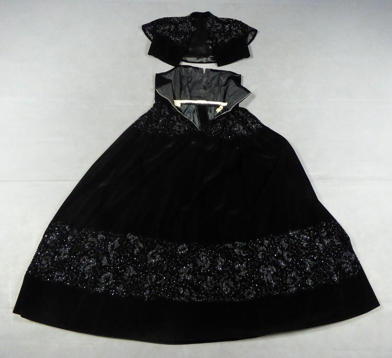 Circa 1950 France  Haute Couture evening set consisting of a dress and a bolero in black silk velvet by Maurice or Roger Worth from the early 1950s. Embroidery work on the shoulders, waist and bottom of the dress with black jet beads in volute