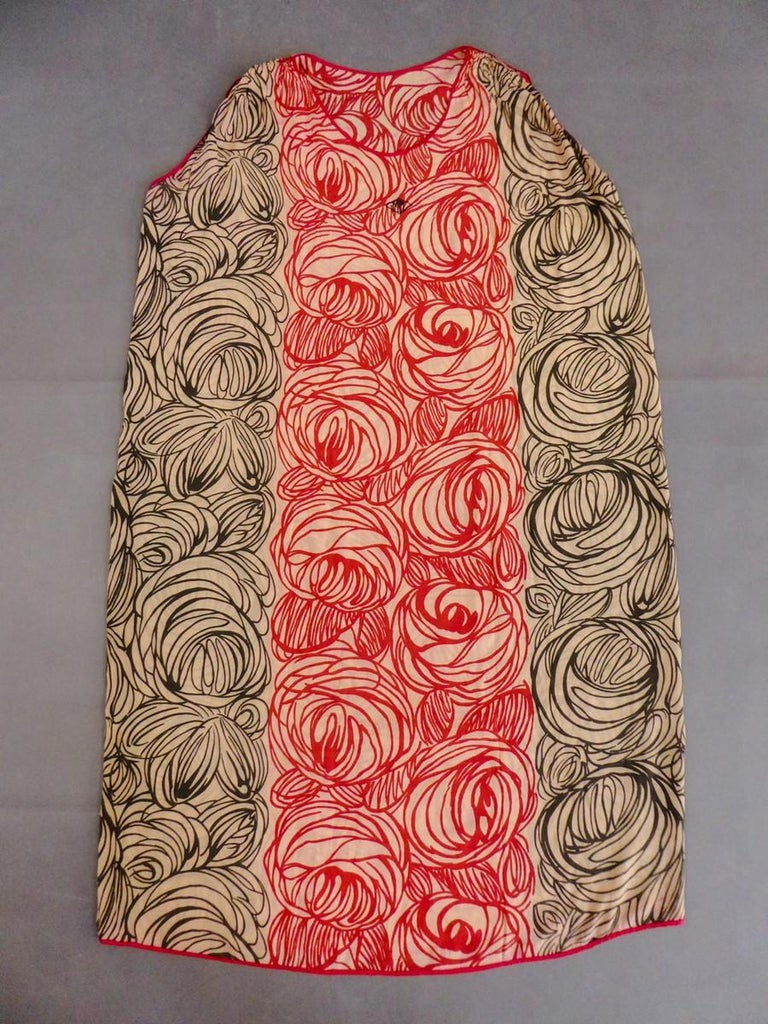 France-Paris Circa 1915  A sleeveless and straight Sac day dress designed by Raoul Dufy for the Atelier Martine. Cream pongee silk printed with stylized generous roses alternately in red and black. Small embroidered diamond shape on the chest signed