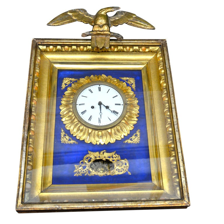 A traditional Austrian Biedermeier wall clock featuring a rectangular carved and gilded wood frame clock face; surmounted by a gilt bronze winged eagle. The decorations on the frame are of gilded metal with gilded carved wood around the dial. The