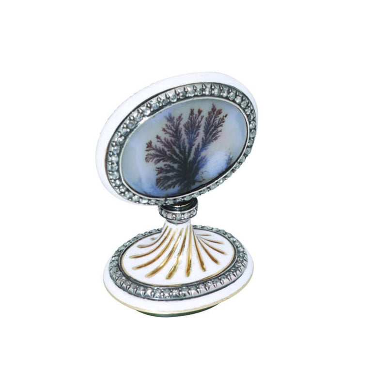 A Faberge' jewelled and enamelled gold and hardstone seal, the flat oval handle inset at both sides with a moss agate panel over sunburst engine-turning within a rose-cut diamond-set border, the mount enamelled in opaque white, the collar with