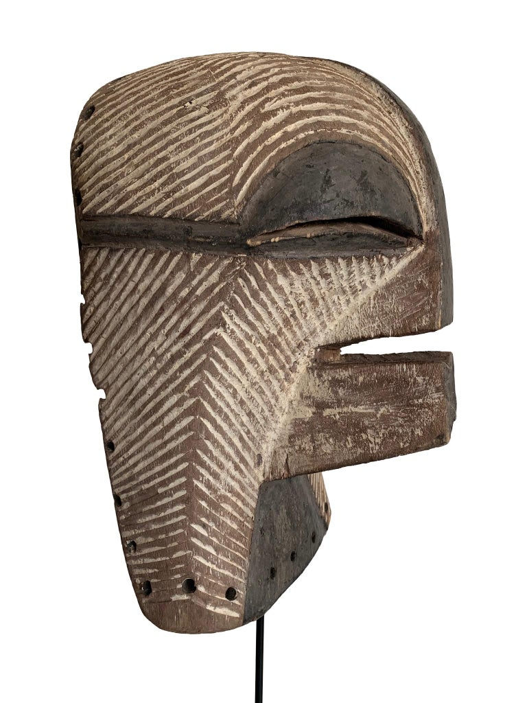 A female Songye Kifwebe hand carved wooden ceremonial mask. The wooden mask is carved with geometric lines on the face and head which are whitened with pigment and darkened on the large ridged nose, mouth and eyes. Around the back edge are the holes