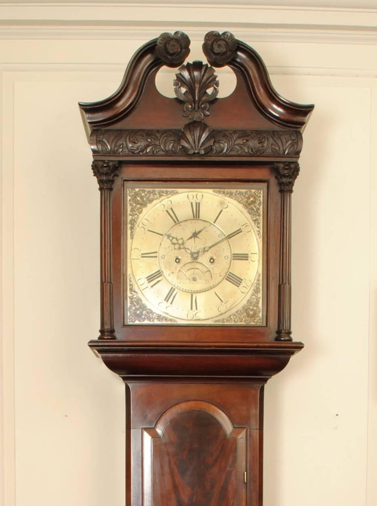A fine example of an 18th century mahogany long case clock with fantastic carved details to the hood and a flame mahogany door, the eight day movement with full bras dial signed Samuel Bailie of Dromore. The Baillie family had a number of clock