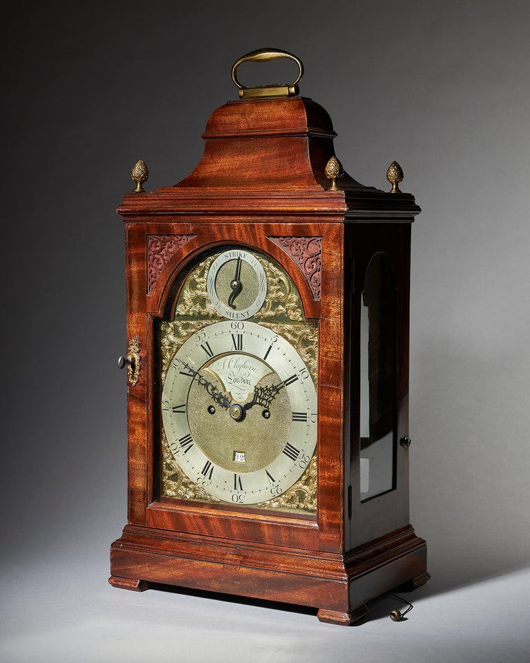 An 18th century English spring-driven mahogany table clock, signed on both the dial and the backplate S. Cleghorn London, made circa 1770-1775. The case is of classical shape for the period, with a bell top, arched doors to the front and rear, and