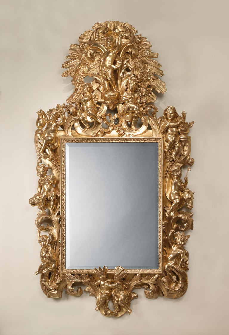 A fine and decorative Italian giltwood mirror carved with allegorical figures of the continents and the seasons. 