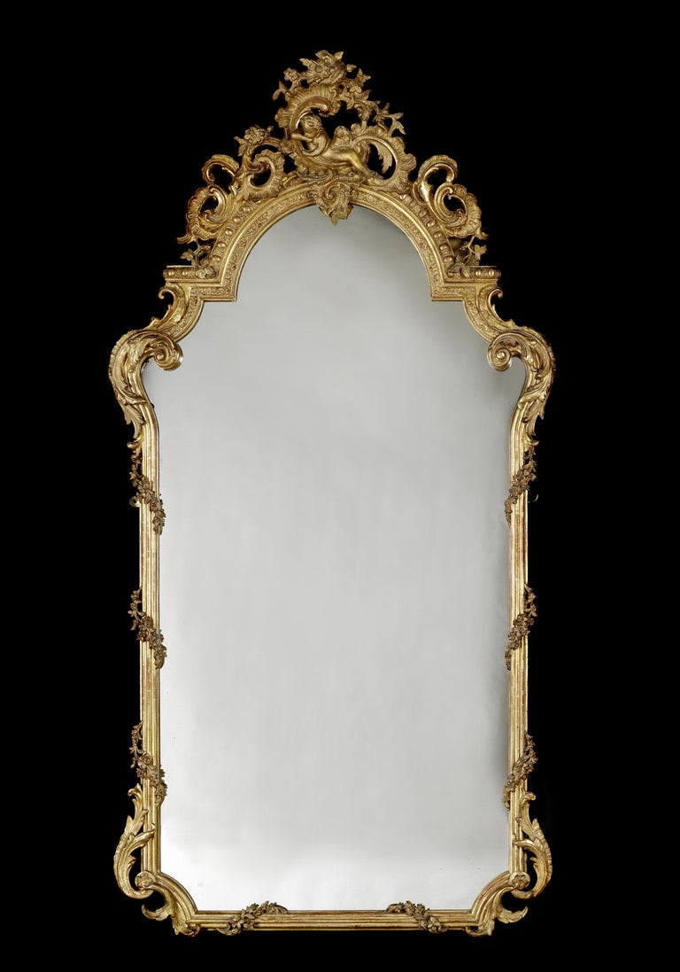 A fine and tall Louis XV style carved giltwood mirror.   French, circa 1870.  This very finely carved mirror has an arched cresting expressively carved with acanthus 'C'-Scrolls and rock roses centred by a reclining putti. The reeded uprights