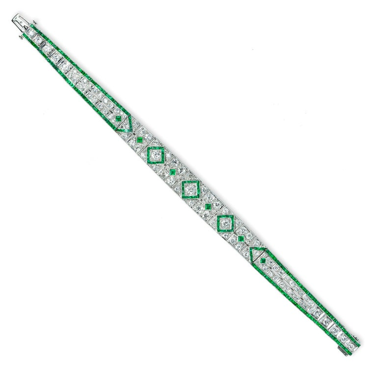 A fine Art Deco emerald and diamond bracelet, the twenty eight openwork panels of geometric design set calibre-cut emeralds weighing approximately a total of 1.20 carat and old cut diamonds weighing approximately a total of 4.75, all set in