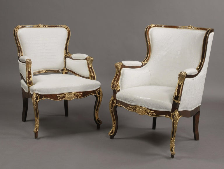 A fine companion pair of Russian gilt bronze-mounted armchairs.   Russian, circa 1870.  The frame of each chair with exceptional gilt bronze mounts. The padded backs, seats, sides and arms later upholstered in crocodile pattern white leather.