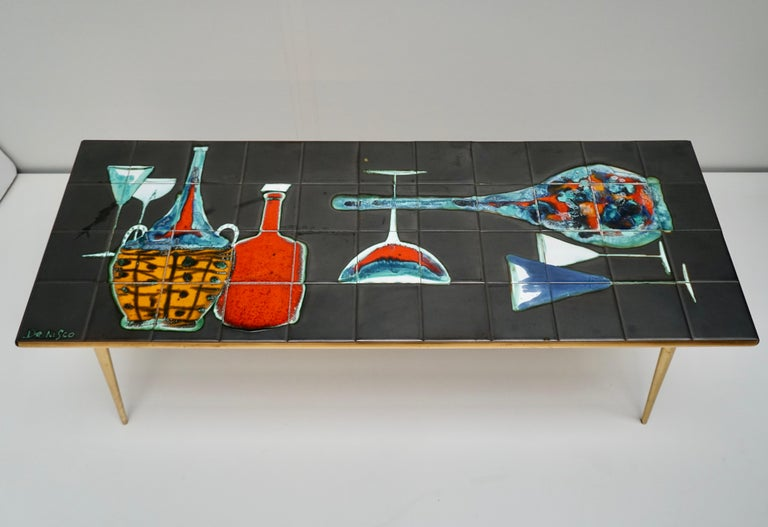 A fine Belgium 1950s coffee table decorated with colorful bottles and glasses. Enameled ceramic tile top on a brass base, signed Denisco.  Width 119 cm. Depth 44 cm. Width 45 cm.