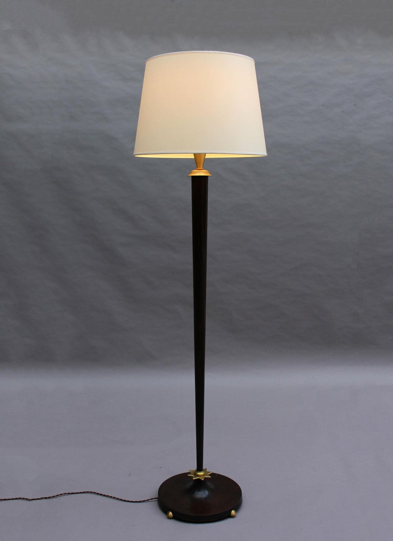With a brown patinated round base and tapered stem, embellished with gilded accents, and a new shade.