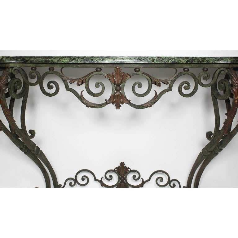 A French Louis XV style wrought iron wall-mounting console with marble top. The scrolled serpentine wrought iron frame with its original verde-green finish and voluted front support legs on tapered scrolled feet, surmounted with patinated gilt