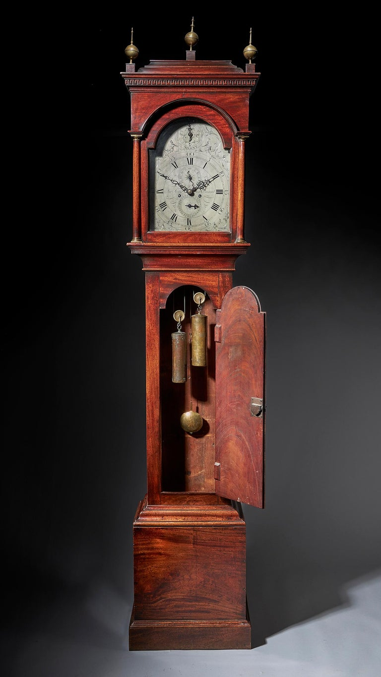 A fine George III period mahogany longcase clock of excellent colour, patination and proportions, circa 1780-1790  Surmounted with three ball and spike brass finials, the inverted bell top hood is decorated with a Greek key frieze below an ovolo