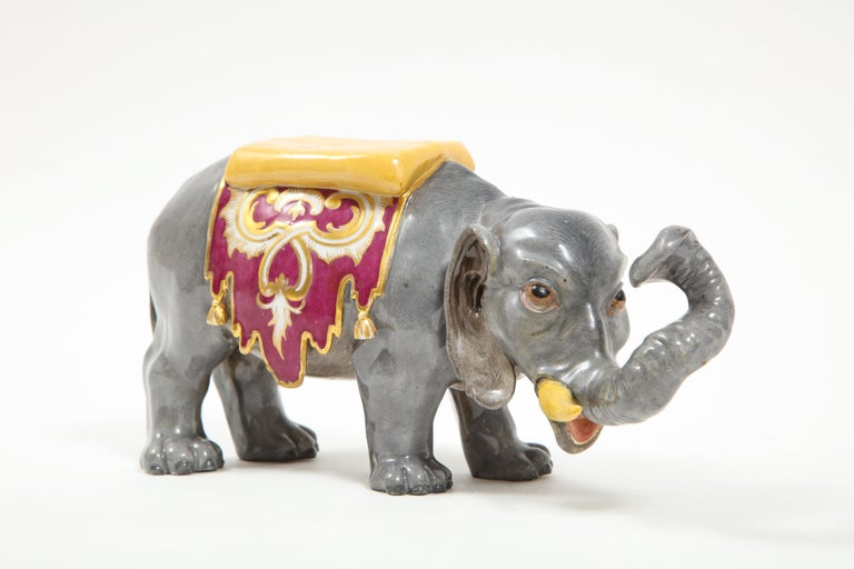 A fine 19th century Realistically hand-carved German Meissen Porcelain model of an elephant with a saddle. Modeled in the Indian taste, this elephant is hand-carved and hand-painted by the finest artist's at Meissen. The quality and craftsmanship is