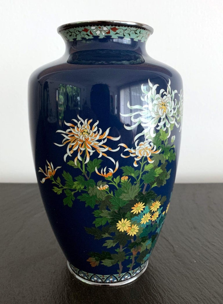 A Japanese cloisonne vase of fine quality by the workshop of Hayashi Kodenji (1831-1915) dated to early 20th century 1910s-1930s. In a mid-night dark blue background that the artist was known for, an arrangement of a variety of chrysanthemum flowers