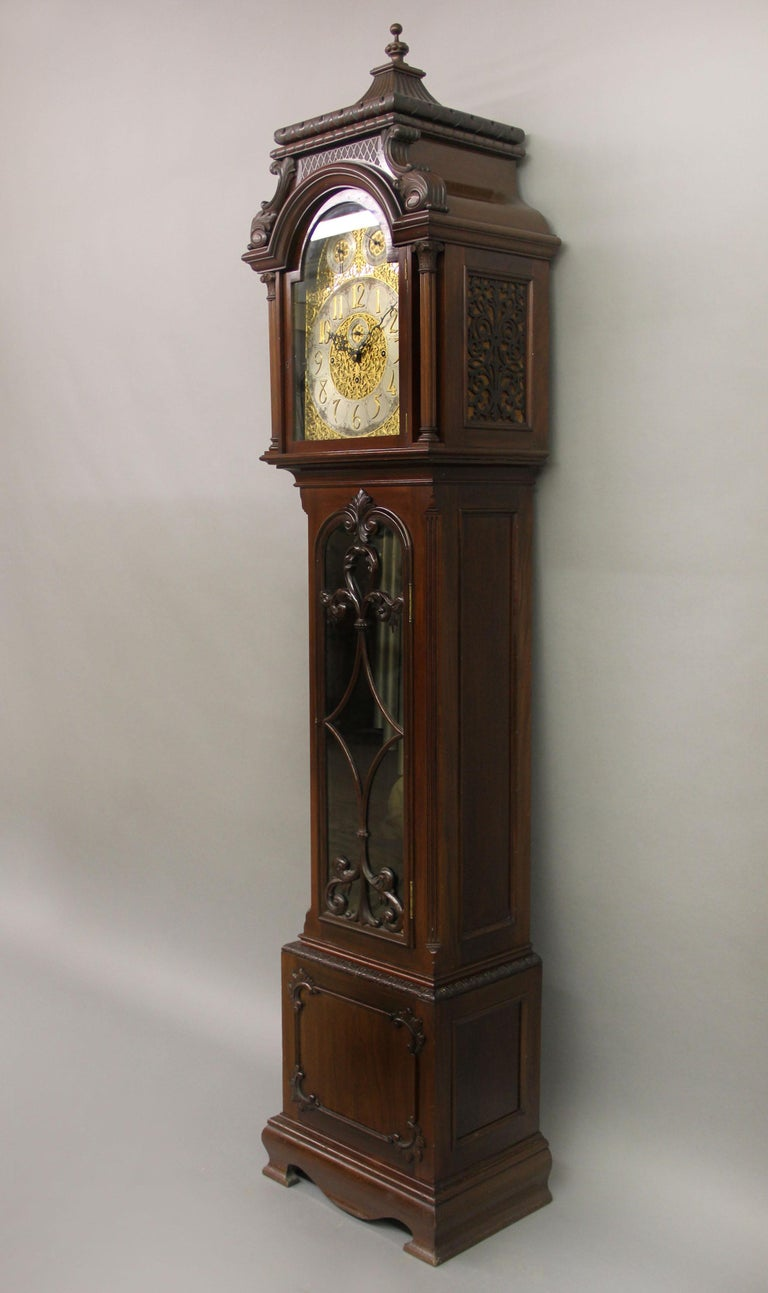 A fine late 19th century English carved nine tube longcase grandfather clock  The clock with an eight day movement and chiming on nine tubes. The very elaborate designed face with Arabic Numerals enclosing a subsidiary seconds dial in the center,